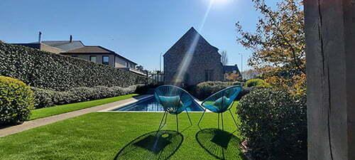 Rustgevende tuin met zwembad en kunstgras
